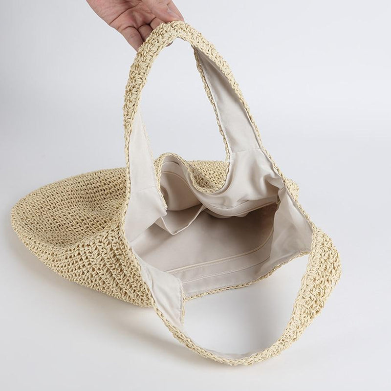 Image shows a person holding one of the shoulder straps on the sloughy tote so the inside is visible. The bag is lined on the insidde and there is a small pocket.