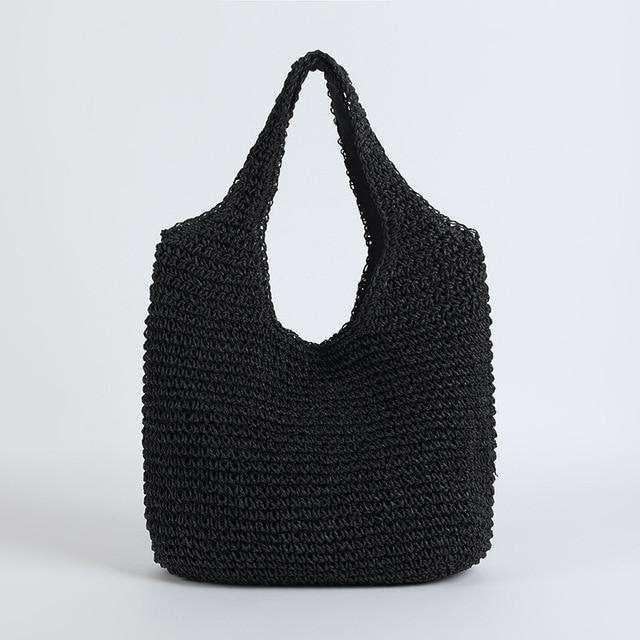 Image shows the slouchy tote in black. It has a simple shoulder tote shape and both bag and shoulder straps are woven in straw. It has a slouchy unstructured shape and is plain and unembellished.