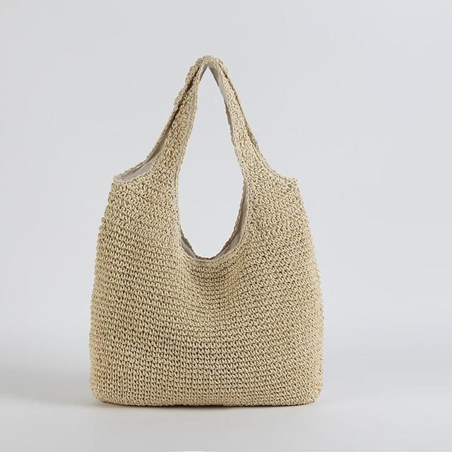 Image show the slouchy tote in sand. It is a simple shoulder tote shape and both bag and shoulder straps are woven in straw. It has a slouchy unstructured shape and is plain and unembellished.