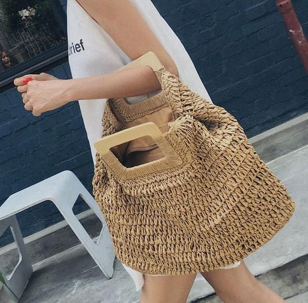 A woman walks along the street holding the straw tote bag in coffee. The bag is woven in straw and is oversized and slouchy. The handles are oblong in shape and made from wood.
