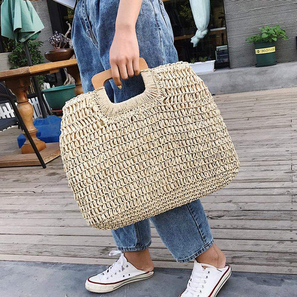 A woman is holding the straw tote bag in toe toe. The bag is woven in straw and is oversized and slouchy. The handles are oblong in shape and made from wood.