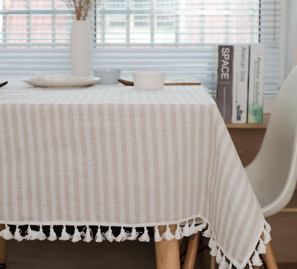 Image shows a tablecloth on a table with a white chair. The tablecloth is beige and white striped with tassels along the edge.