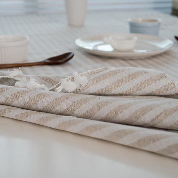 This image is a close up of a beige and white striped table cloth folded on a table.