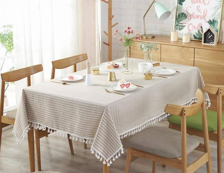 Image shows a tablecloth on a table with four chairs. The tablecloth is beige and white striped with tassels along the edge.