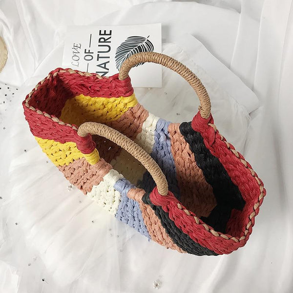 The bag is a half moon shape with round handles. The bag is woven straw and has different colours in pizza segments - pink, blue, yellow, white and red. The inside of the bag is visible and it is unlined.