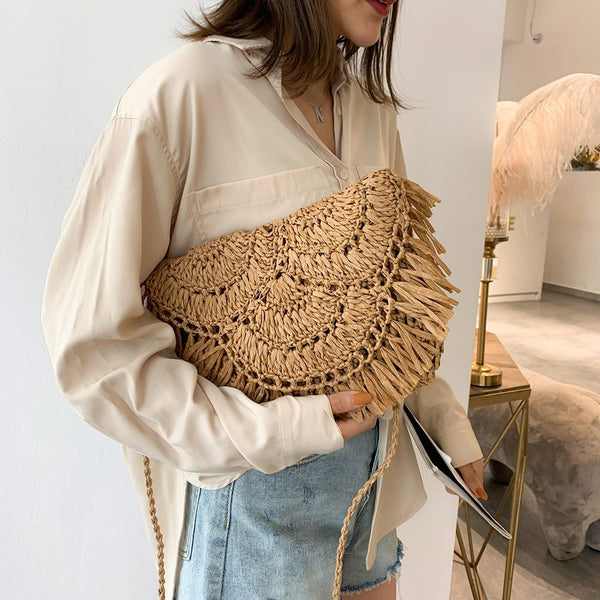 Image shows a woman in denim cutoffs ad a shirt holding the waiheke cross body bag like a clutch. The bag is shaped like an envelope and the fold over has tassels alond the edge.