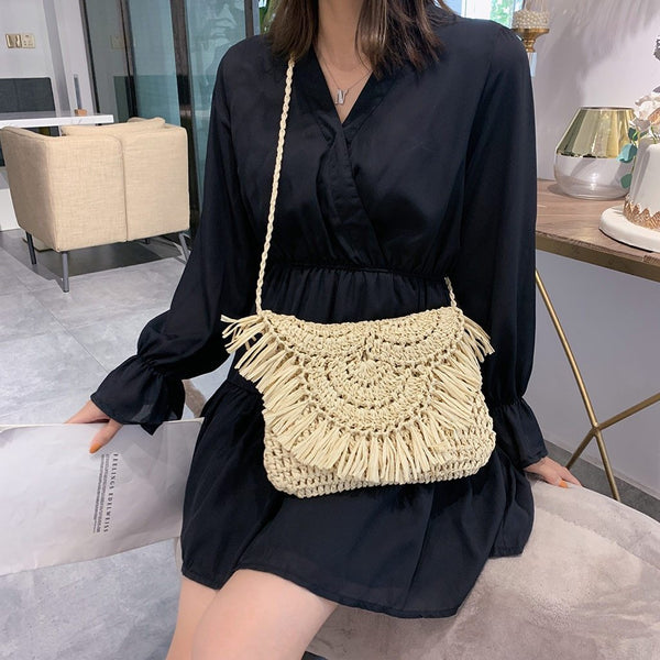 A woman wears a black dress and the waiheke bag. The bag has a long crossbody handle. The bag has a old over flap which has tassels along the edge of it. The bag is woven in a textured patterm.