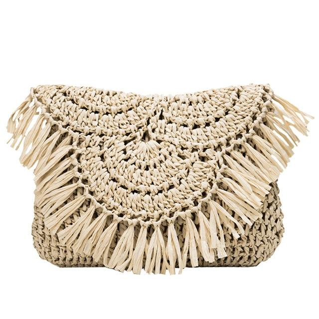 The image shows the waiheke crossbody bag in sand. It is shaped like an envelope and the fold over flap has tassels along the edge of it. The bag is woven in straw and in a pattern.