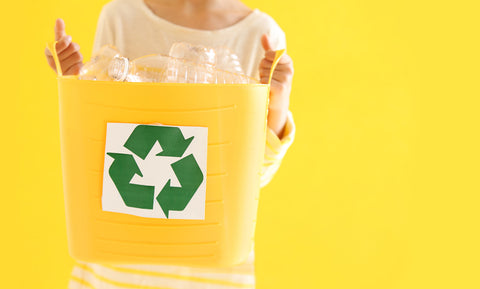 Person holding yellow recycling bin