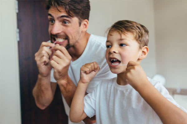 Dad and son flossing with silk dental floss