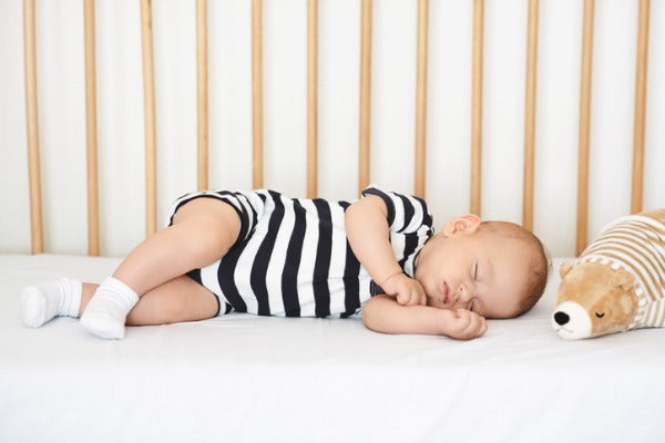 baby sleeping on fitted sheet