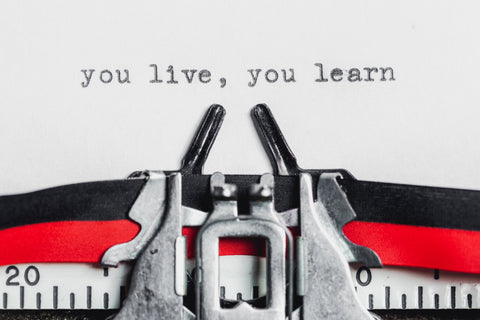 typewriter and paper with wording - you live, you learn