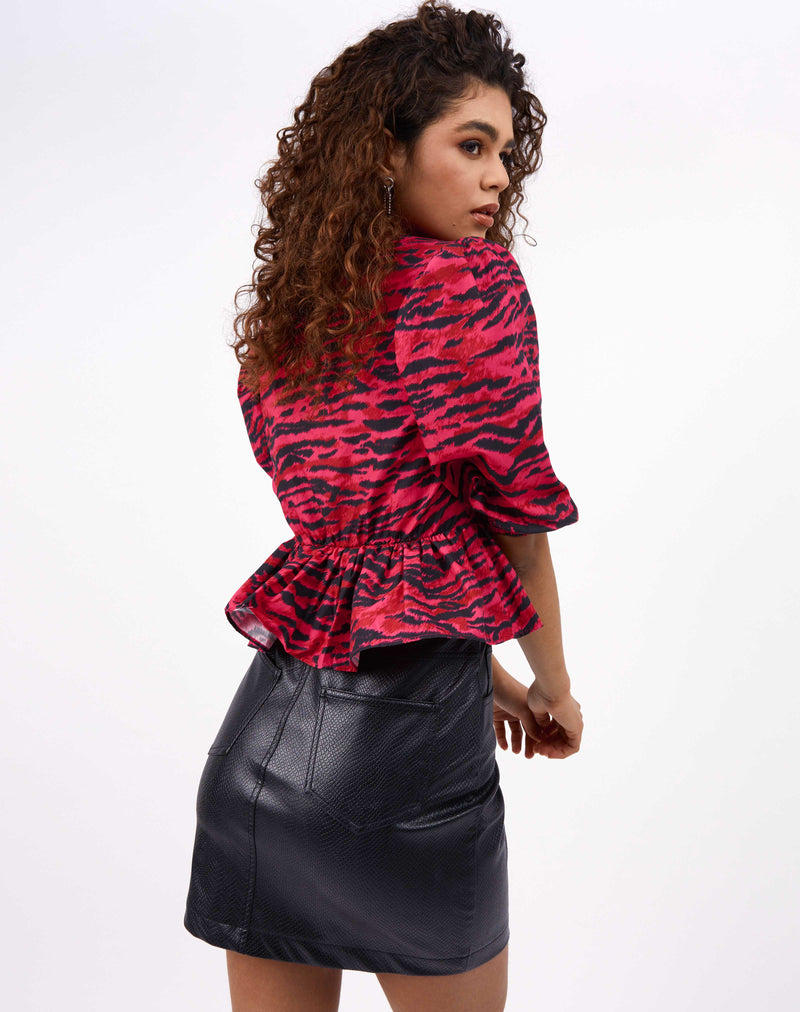 the model looks over her shoulder in the ava puff sleeve pink animal print top showing the peplum over a PU mini skirt