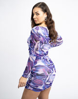 the model is looking over her shoulder showing the back of the daphe swirled purple mesh mini dress with long sleeves and mini length