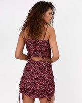 the model wears the dani floral ruched front top with matching skirt while facing away from the camera
