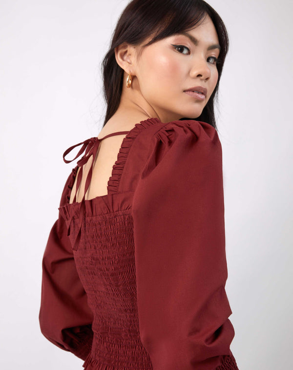 model looks over her shoulder showing the back tie of the mia burgundy shirred blouse