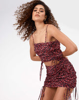 the model wears the dani floral ruched front top with matching skirt while leaning towards the camera with her hands behind her back and hair blowing