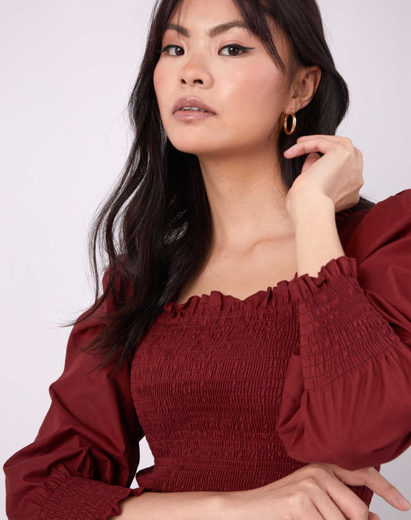 close up image of model with hand to her ear in the mia burgundy shirred blouse