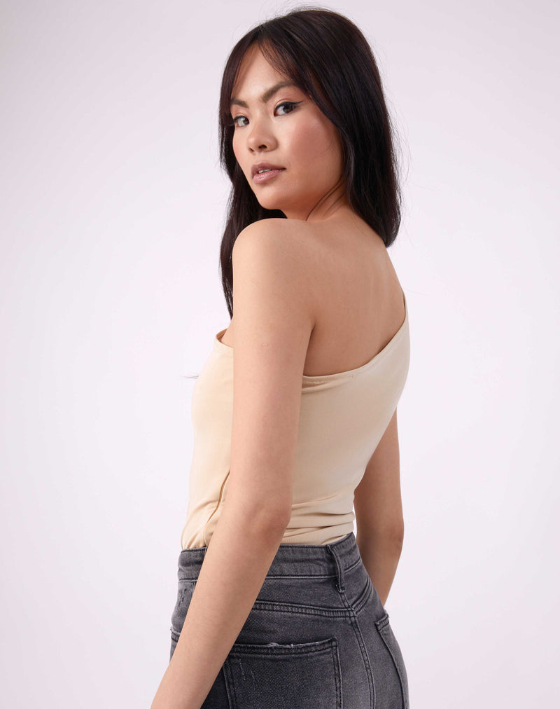 model looks over her shoulder in isla birch one shoulder bodysuit worn with grey jeans