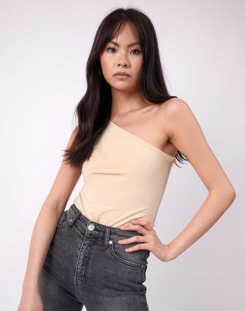 model with hands on her hips in isla birch coloured one shoulder bodysuit with grey jeans
