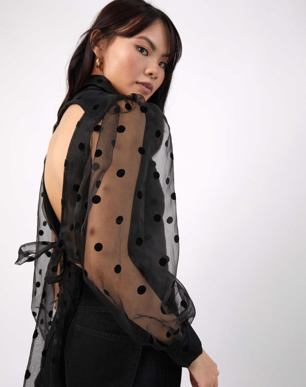 model looks over her shoulder in the fifi sheer sleeve polka dot blouse with an open back