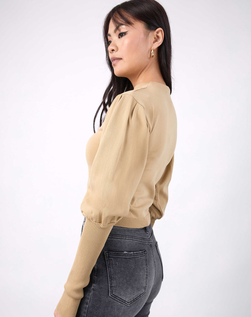 model looks over one shoulder the nina balloon sleeve knit top in beige