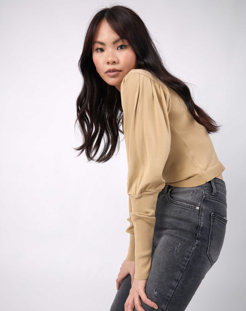 model bends forwards with hands on her knees the nina balloon sleeve knit top in beige and grey jeans