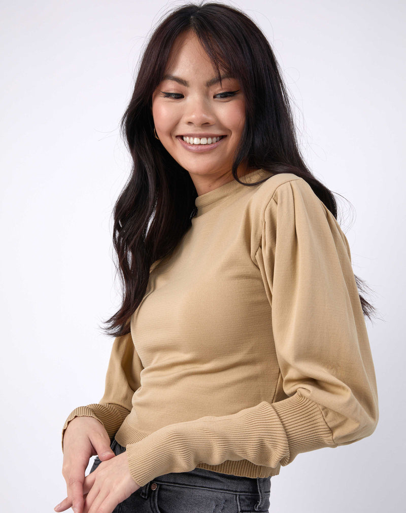model smiles with her arms in front in a cropped image wearing the nina balloon sleeve knit top in beige
