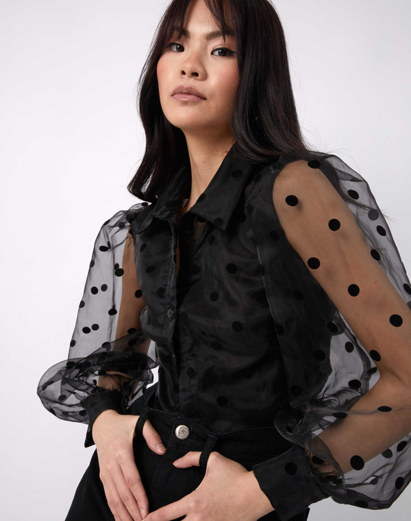 model poses with hands in the pockets of her black jeans while wearing the fifi sheer polka dot blouse with collar and long sleeves