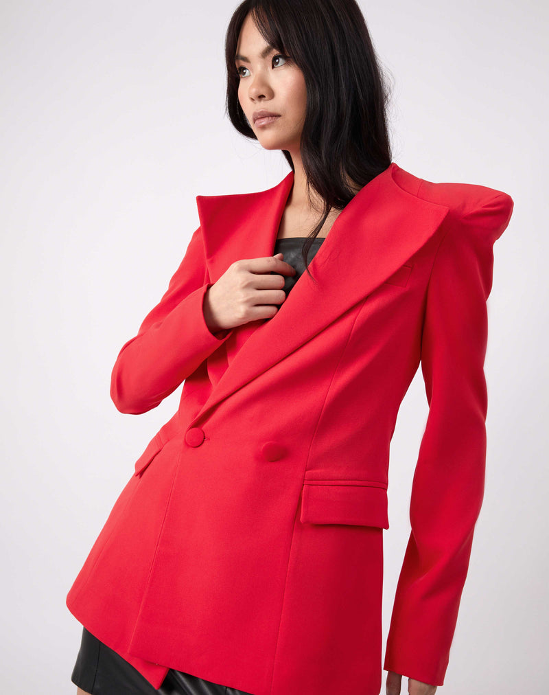 model holds her hand to her chest while wearing the Quinn Red Double Breasted Blazer over a pu dress