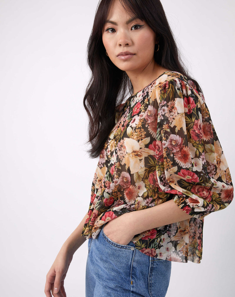 a cropped image of the model with her hand in the pocket of her blue jeans wearing the floral floral sheer puff sleeve top