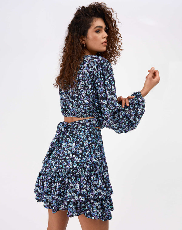 model faces away from the camera and holds her arm wearing the Maeve Tie Back Floral Top and matching skirt