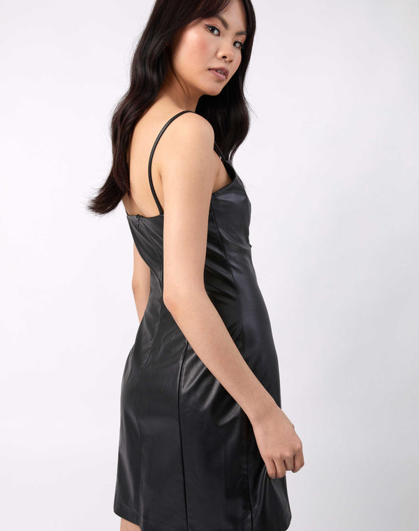 the model looks over her shoulder showing the back of the Ray Faux Leather Mini Dress in Black