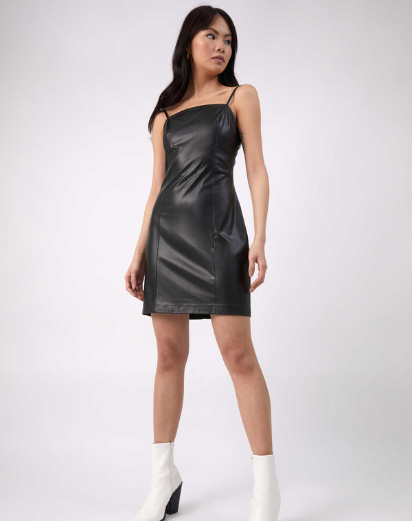 a full length shot of the model wearing the Ray Faux Leather Mini Dress in Black with white boots