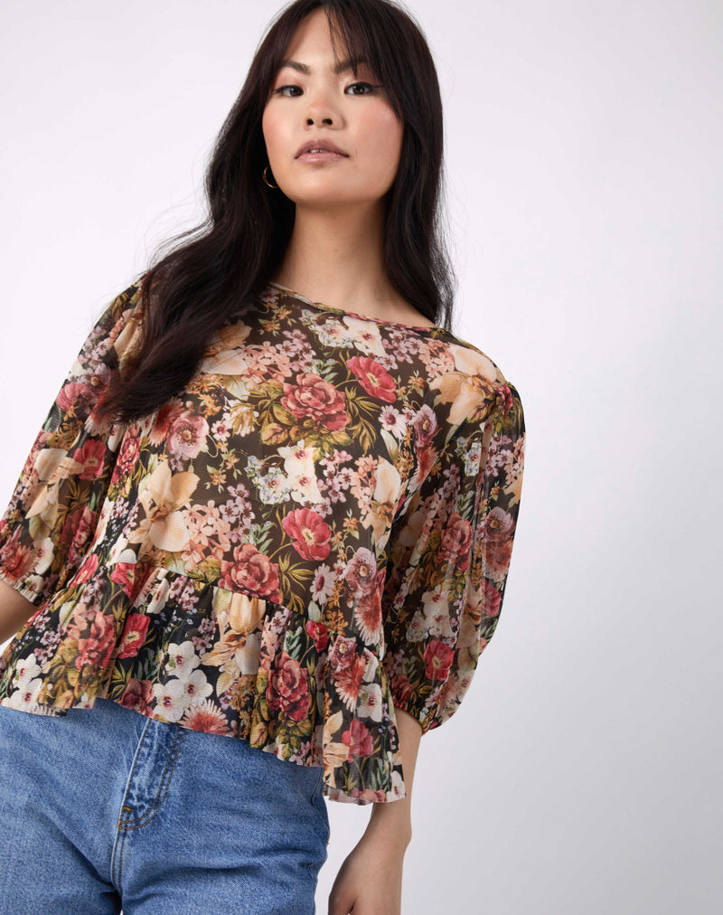 an angled crop shot of the model wearing the flora multicoloured floral sheer puff sleeve top with frill and blue jeans