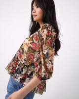 a cropped image of the model from the side in the flora floral sheer puff sleeve top with blue jeans