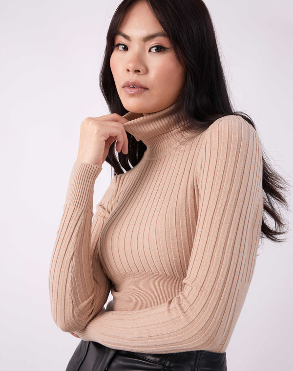 model pulls on the neck of the Vlona Beige Turtleneck Ribbed Knit