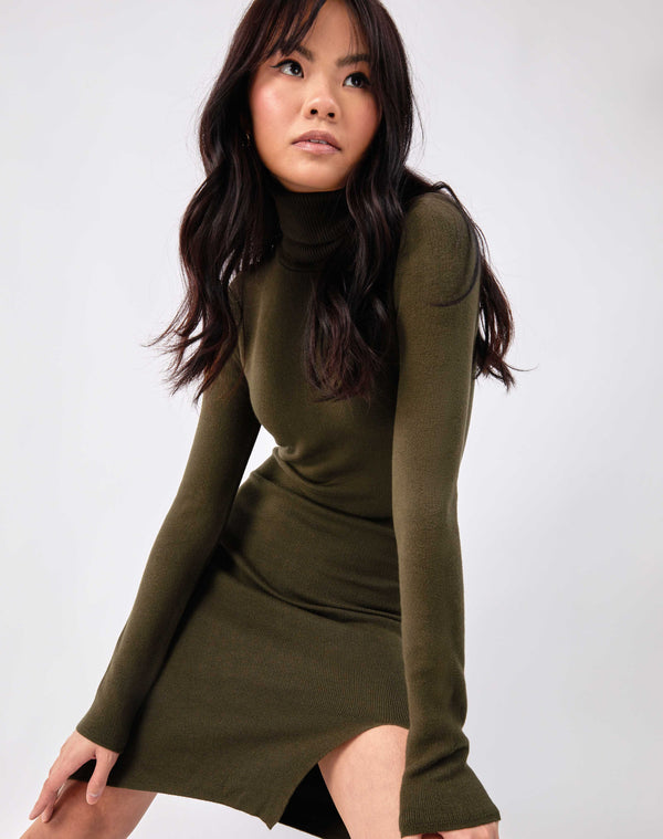 model leans forward towards the camera with hands on her knees in the liana olive green roll neck knit midi dress