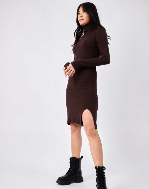 model looks off camera with hands in front of her in the liana brown roll neck knit midi dress with military style boots