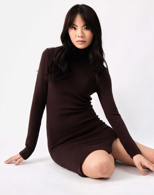 model sits on the floor looking at the camera in the liana brown roll neck knit midi dress