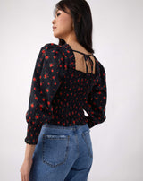 model looks away from camera wearing the mia red rose print shirred blouse with blue jeans, showing the tie back
