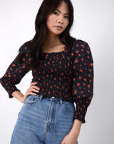 model has hand on hip wearing the mia red rose print shirred blouse