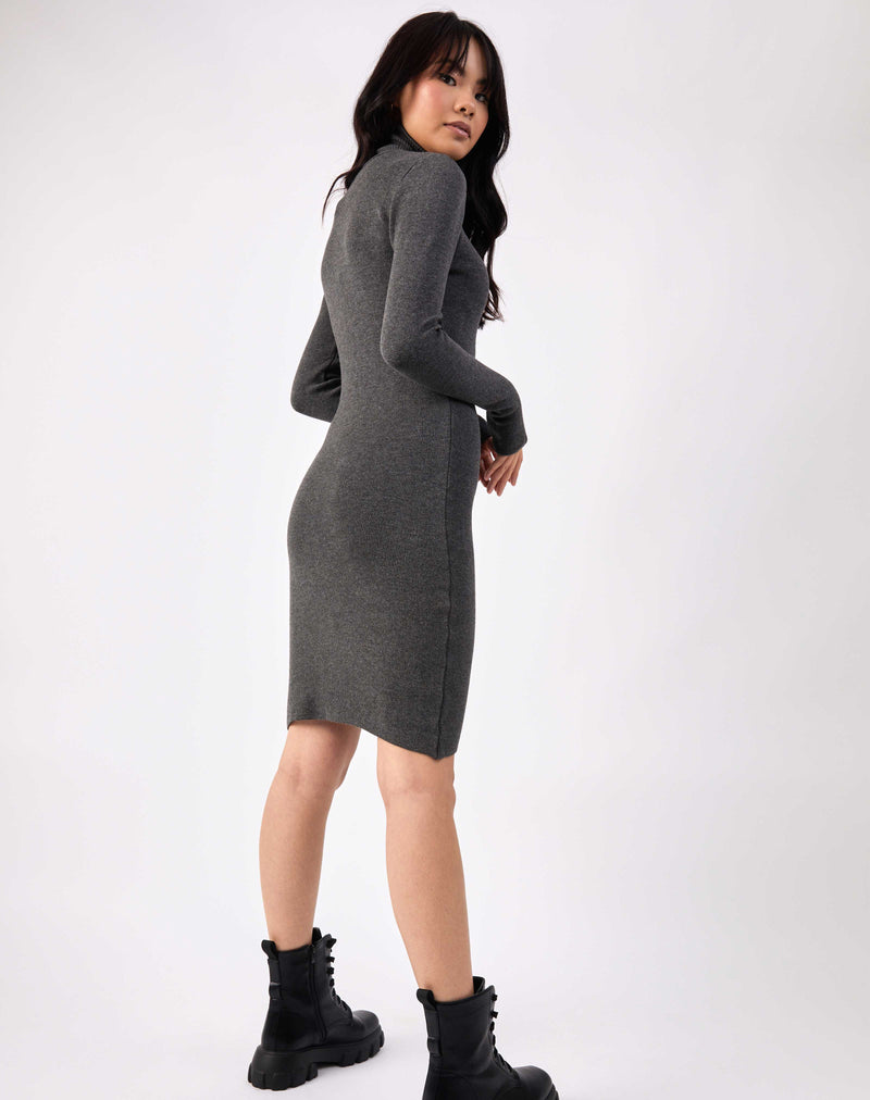 model faces away from the camera with arms in front in the liana grey roll neck knit midi dress with military boots