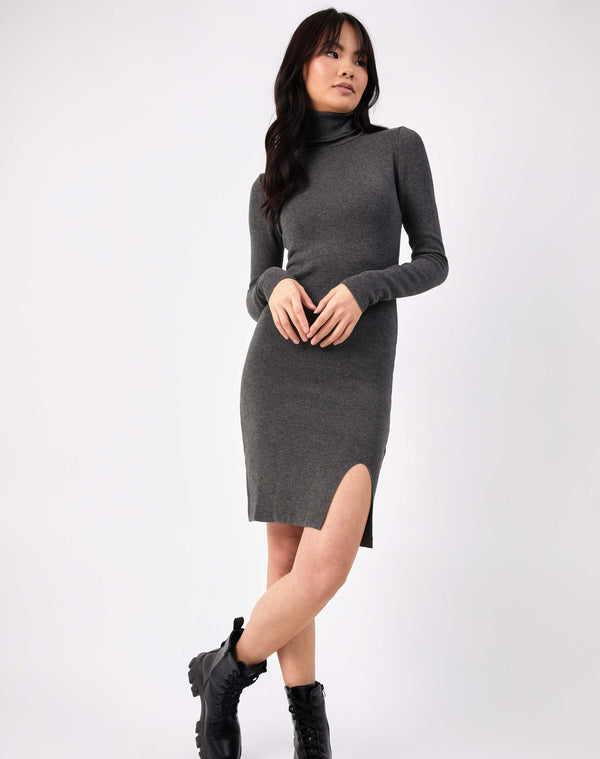 model crosses her arms in full length image in the liana grey roll neck knit midi dress with legs crossed in military boots
