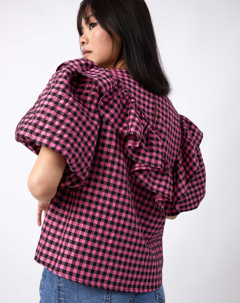 model shows the back of the laila pink and black check frill top with puff sleeves worn with blue jeans