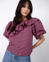 a cropped image of the model with her hands behind her wearing the laila pink and black check frill top with blue jeans