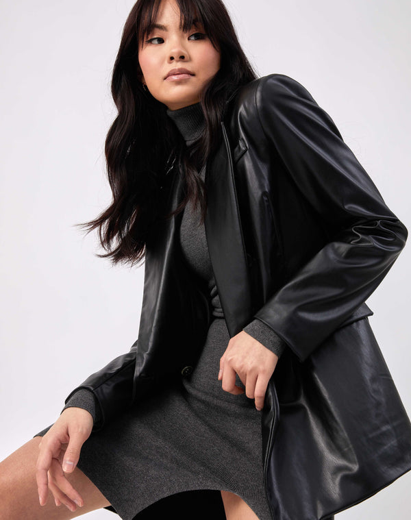 the model sits while wearing Rela Black Faux Leather Blazer over a knitted grey dress