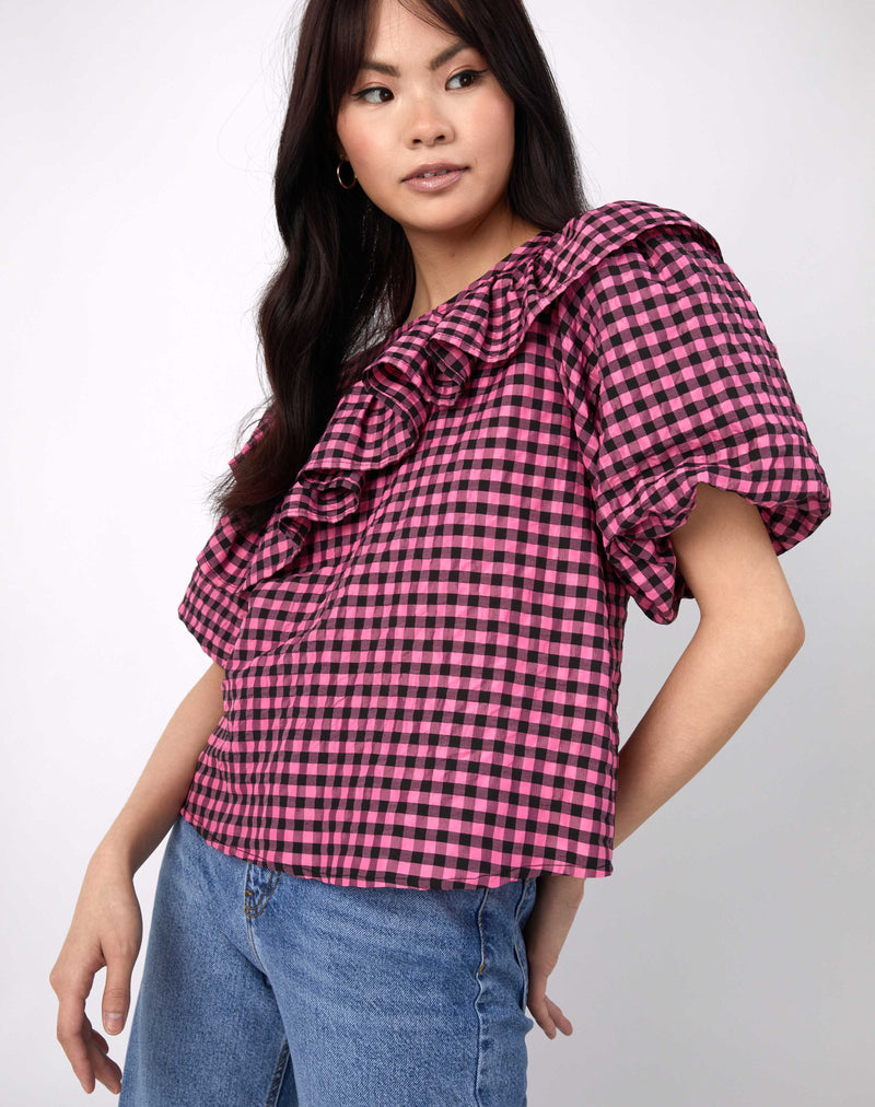 model looks away from camera wearing the laila pink and black check frill top with short sleeves along with blue jeans