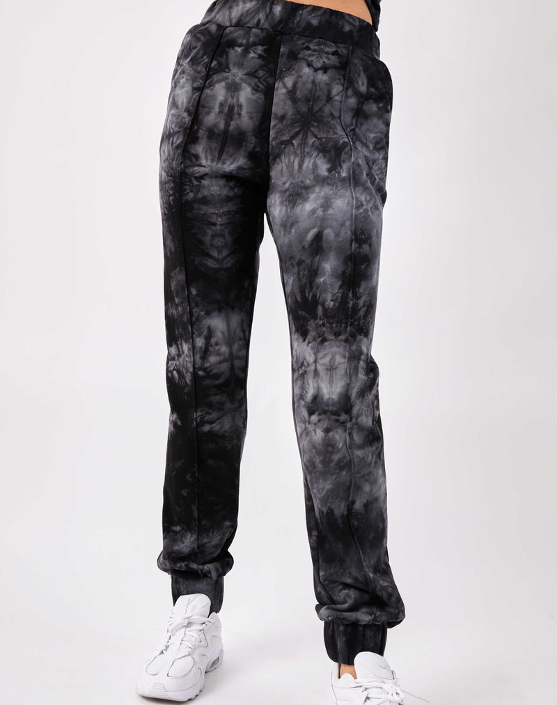 a close cropped image of a model wearing the Saskia Grey Tie Dye Joggers with white trainers