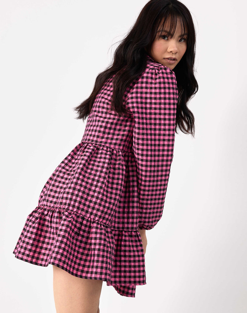 model leans forward wearing pink and black check alice collared dress from the back against white background